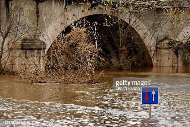 A picture taken on April 1 2013 shows a road sign in a flooded street in Viana de Cega province of Valladolid Spain suffered its wettest March since...