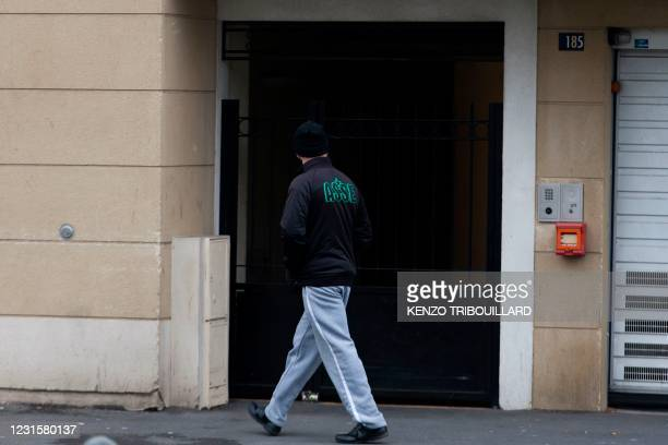 Picture taken on April 1, 2016 shows a man walking past the entrance of the building where lived main suspect in a foiled attack plot Reda Kriket. -...