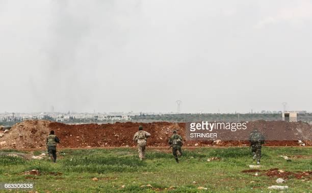A picture taken on April 1 2017 near the town of Qumhanah in the countryside of the central province of Hama shows members of the Syrian government...