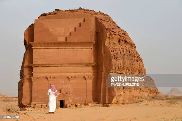 TOPSHOT A picture taken on April 1 2018 shows a man standing outside of the Qasr alFarid tomb carved into rosecoloured sandstone in Madain Saleh a...