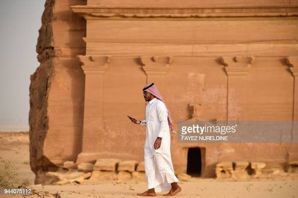 A picture taken on April 1 2018 shows a man standing outside of the Qasr alFarid tomb carved into rosecoloured sandstone in Madain Saleh a UNESCO...