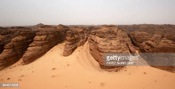 A picture taken on April 1 2018 shows an aerial view of carved rosecoloured sandstone mountains in the desert of alUla in northwestern Saudi Arabia...