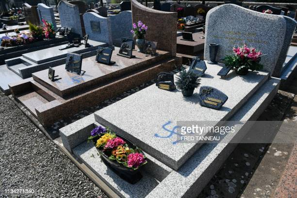 A picture taken on April 1 2019 shows graves vandalised with spraypainted swastikas at a cemetery in Ploermel western France