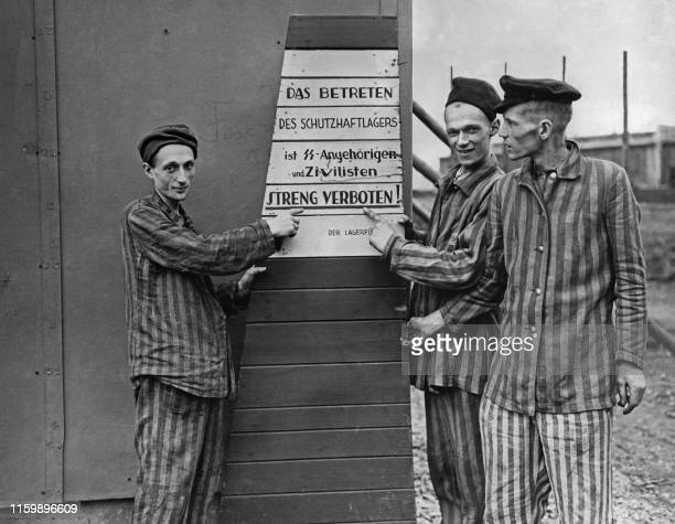 Picture taken on April 10, 1945 at Hanover-Harlen Nazi concentration camp, near Hanover, showing prisoners liberated pointing to a sign taken from...