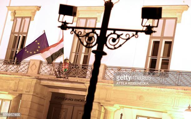 A picture taken on April 10 2017 shows the Hungarian and EU flags outside the Presidential Palace in Buda Castle of Budapest before a demonstration...