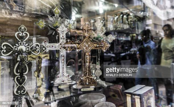 A picture taken on April 11 2017 shows crucifixes on display through the windowpane of a church's paraphernalia shop in Cairo's northern suburb of...