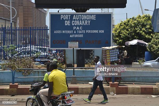 A picture taken on April 13 2016 shows people walking past the sign of the Autonomous Port of Conakry The Bollore group headquarters which houses...