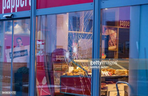 A picture taken on April 13 2018 shows the damaged glass window of a bakery in Fulda western Germany where German police said they shot dead a man...