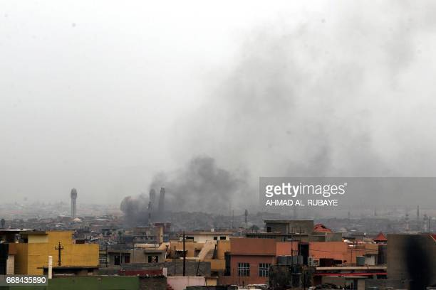 A picture taken on April 14 2017 shows smoke billowing in west Mosul near the Great Mosque of alNuri in Mosul where Islamic State group leader Abu...
