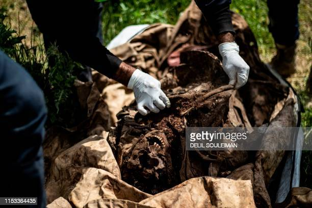 Picture taken on April 14, 2019 shows a member of Raqa Civil Council 's first responders team holding remains found in a mass grave in the northern...