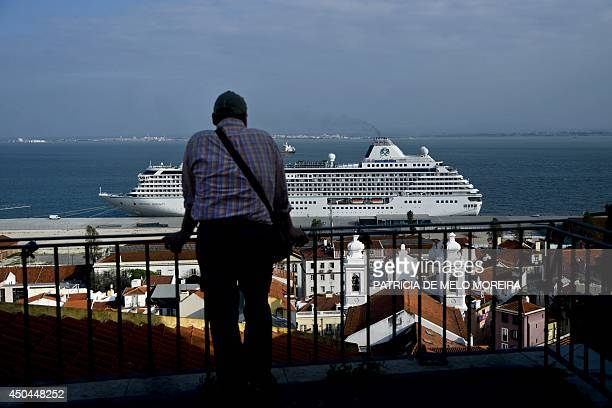 A picture taken on April 15 2014 shows a man looking at a cruise ship from a viewpoint in the Alfama neighbourhood of Lisbon AFP PHOTO / PATRICIA DE...