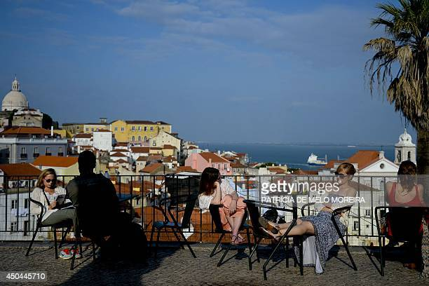 A picture taken on April 15 2014 shows tourists enjoying the sun at an esplanade in the Alfama neighbourhood of Lisbon AFP PHOTO / PATRICIA DE MELO...