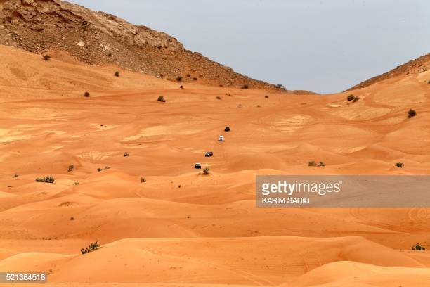 A picture taken on April 15 2016 shows four wheel drive vehicles driving in the desert in the United Emirates of Fujairah / AFP / KARIM SAHIB