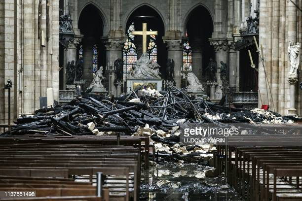 TOPSHOT A picture taken on April 16 2019 shows the altar surrounded by charred debris inside the NotreDame Cathedral in Paris in the aftermath of a...