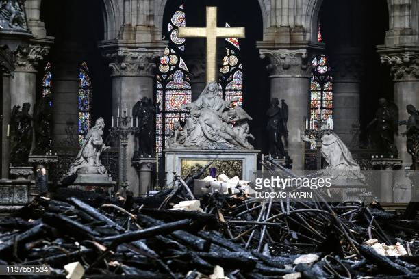 A picture taken on April 16 2019 shows the altar surrounded by charred debris inside the NotreDame Cathedral in Paris in the aftermath of a fire that...