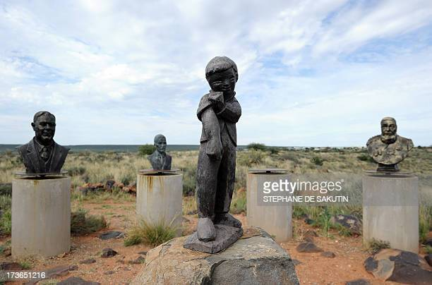 A picture taken on April 17 2013 shows the Orania town's logo of a boy rolling up his sleeves flanked by statues of apartheid heroes displayed above...