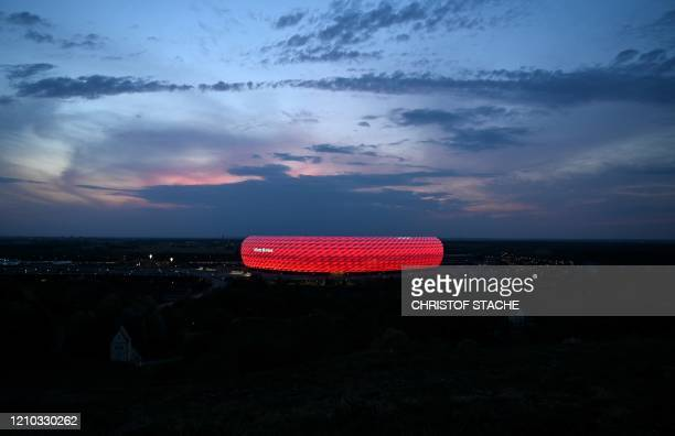 Picture taken on April 17, 2020 shows a view of the Allianz Arena football stadium lighted in red in Munich, southern Germany. - The German first...
