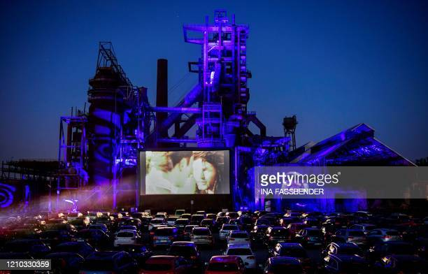 "Picture taken on April 17, 2020 shows cars at a newly opened drive-in cinema in front of the ""Phoenix West"" former blast furnace in Dortmund, western..."