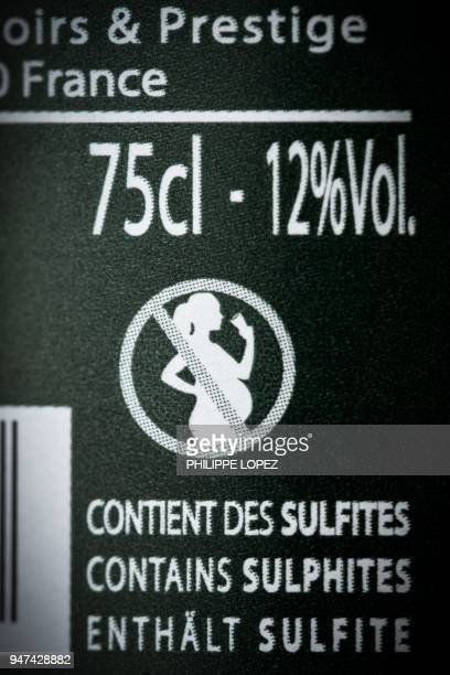 A picture taken on April 17 in Paris shows the label on a French wine bottle with an icon picturing a forbidden sign on a pregnant woman drinking The...