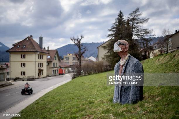 Picture taken on April 18, 2020 in Sainte-Croix shows a scultpure representing a man wearing a facemask as a preventive measure against the Covid-19...