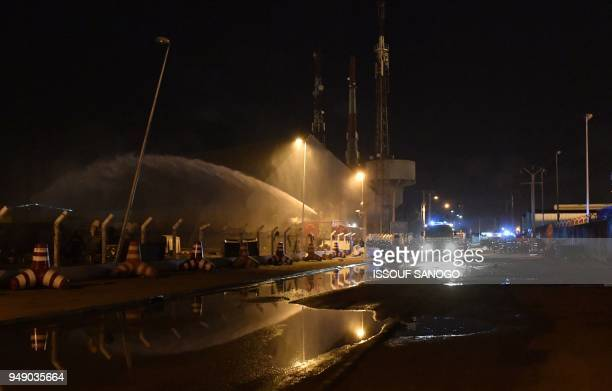 A picture taken on April 19 shows firefighters and security agents working to put out a fire in a tank truck on the parking lot of the Ivory Coast...