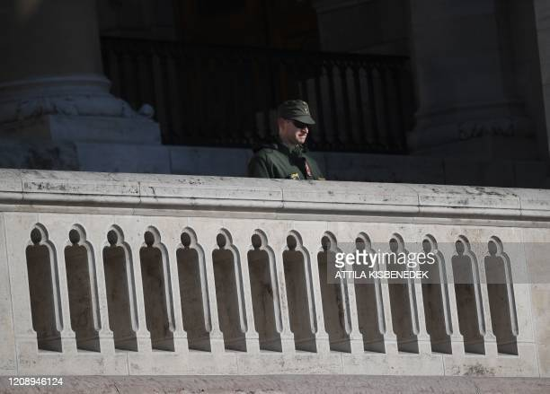 Picture taken on April 2 2020 shows a soldier standing guard in front of the parliament building on the banks of Danube River in Budapest Hungary...