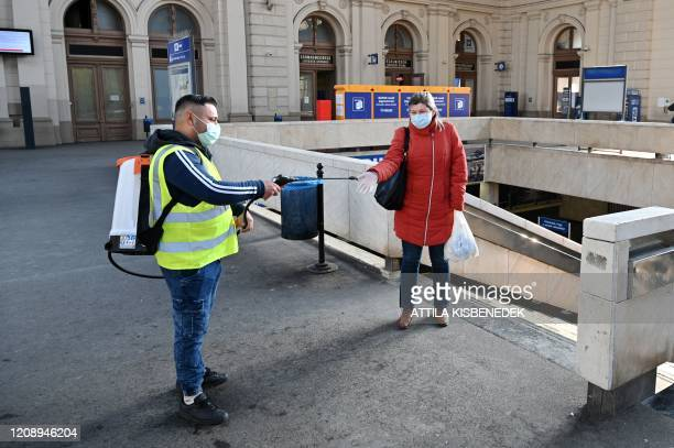 Picture taken on April 2 2020 shows an employee disinfecting the hands of a passenger in Keleti railway station in Budapest Hungary Hungary on April...