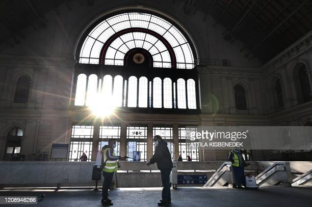 TOPSHOT Picture taken on April 2 2020 shows an employee disinfecting the hands of a passenger in Keleti railway station in Budapest Hungary Hungary...