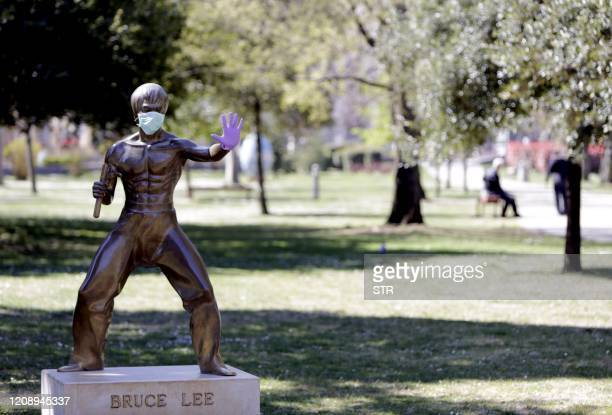 A picture taken on April 2 2020 shows the statue dedicated to martial arts icon and actor Bruce Lee wearing surgical gloves and a face mask in the...