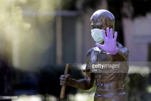 TOPSHOT A picture taken on April 2 2020 shows the statue dedicated to martial arts icon and actor Bruce Lee wearing surgical gloves and a face mask...