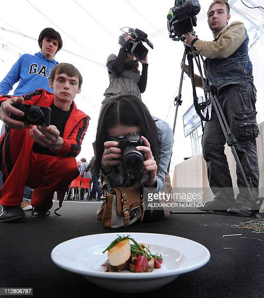 PERONA picture taken on April 21 2011 shows participants of the Omnivore food festival taking pictures of a dish by French chef Julien Burlat in...