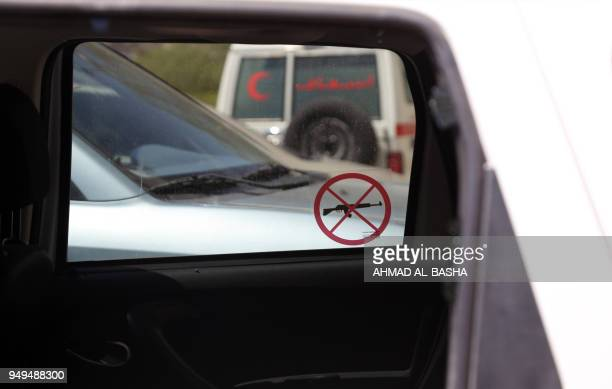 """Picture taken on April 21 shows a """"no weapons allowed"""" sticker hanging on the window of a damaged Red Cross vehicle that was carrying Red Cross..."""