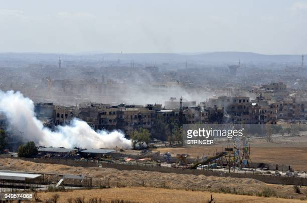 Picture taken on April 21 shows smoke billowing from the Palestinian camp of Yarmuk during regime strikes targeting the Islamic State group in the...