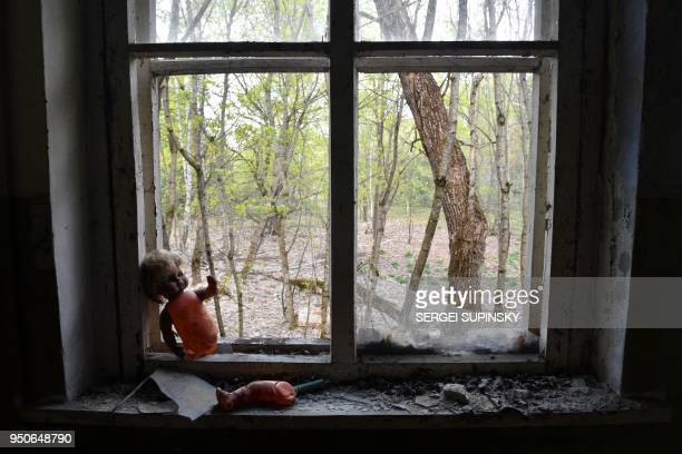 A picture taken on April 23 2018 in the ghost village of Kopachi near Chernobyl Nuclear power plant shows an abandoned kindergarten visited by...