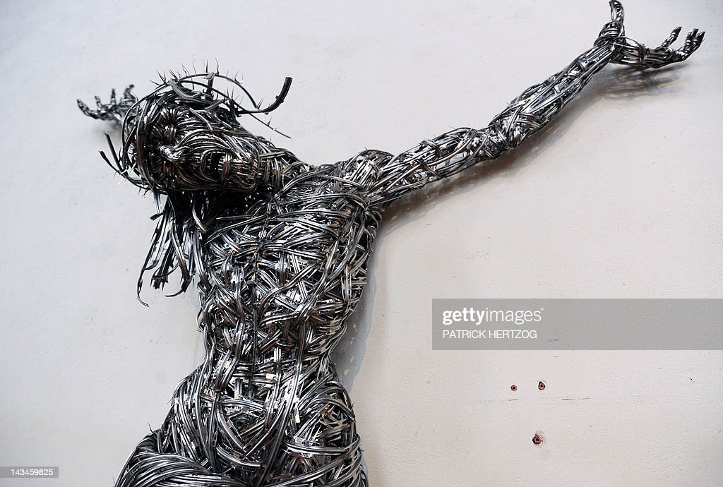 A picture taken on April 24, 2012 shows a contemporary sculpture untitled 'Decor' by Algerian artist Adel Abdessemed on April 24, 2012 at the chapel of the Unterlinden museum in the northeastern French city of Colmar, exhibited besides the 'Isenheim Altarpiece' (aka 'retable d'Issenheim' in French) by German Renaissance painter Matthias Grunewald, as part of the 500-year anniversary of this famed Renaissance religious work. Abdessemed borrowed the image of Christ crucified from Mattias Grünewald to create four crucified Christ, laced with industrial grade razor wire. His work will be shown for the first time in Europe from April 27 to September 16, 2012 in Colmar.