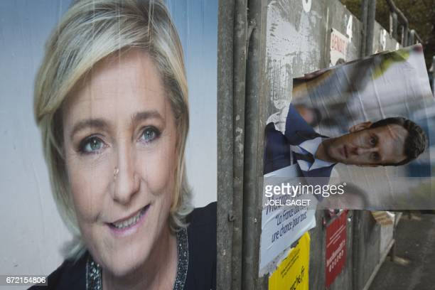 A picture taken on April 24 2017 in HeninBeaumont northern France shows campaign posters of French presidential election candidate for the farright...