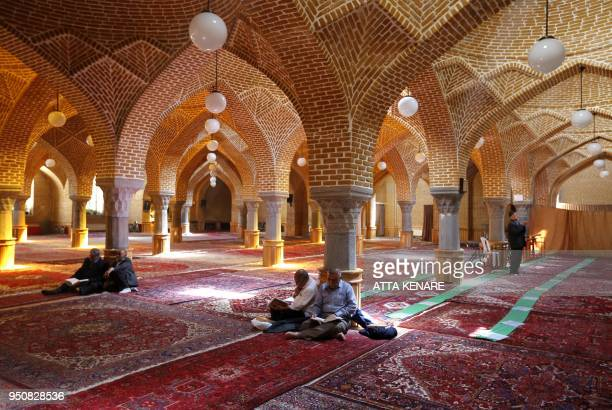 Picture taken on April 24, 2018 shows Iranians reading the Quran as they sit in a mosque in the city of Tabriz in Iran's northwestern East-Azerbaijan...