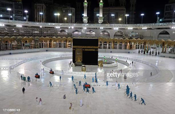 TOPSHOT A picture taken on April 24 shows sanitation workers disinfection the area arround the Kaaba in Mecca's Grand Mosque on the first day of the...