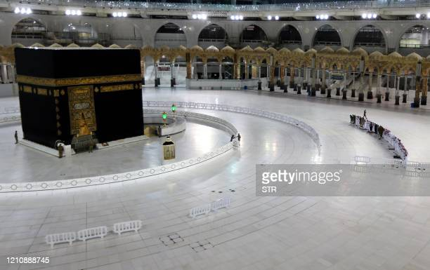 A picture taken on April 24 shows Saudi men performing prayers next to the Kaaba in Mecca's Grand Mosque Islam's holiest site on the first day of the...