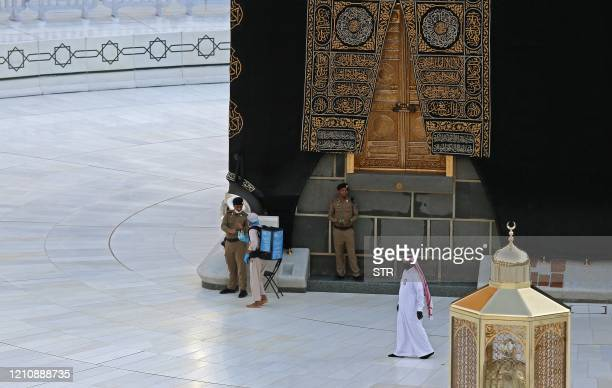 A picture taken on April 24 shows Saudi policemen standing guard next to the Kaaba in Mecca's Grand Mosque on the first day of the Islamic holy month...