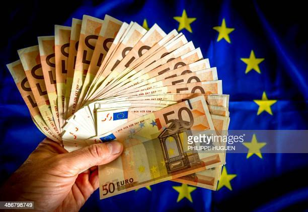 A picture taken on April 25 in Lille shows 50euro notes displayed on an European Union flag European Central Bank chief Mario Draghi said recently...