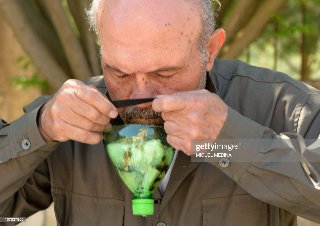 A picture taken on April 26, 2013 shows Abu Tarek, a 74-year-old retired army officer, trying on a homemade gas-mask assembled using a plastic bottle, coal, cotton, gauze, cola, and cardboard, for protection against chemical weapons, in Syria's northern Latakia province. The emerging allegations of likely chemical attacks by Assads regime have stirred outrage around the world, piling pressure on the Obama administration for a military intervention in the messy conflict. AFP PHOTO / MIGUEL MEDINA / AFP PHOTO / Miguel MEDINA
