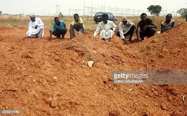 A picture taken on April 26 2016 shows members of the Islamic Movement of Nigeria a Shiite group pray at a mass grave in the outskirts of northern...