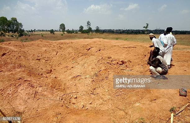 A picture taken on April 26 2016 shows members of the Islamic Movement of Nigeria a Shiite group praying at a mass grave in the outskirts of northern...