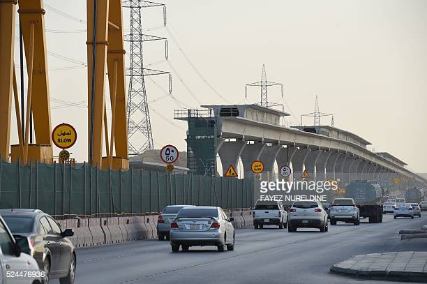A picture taken on April 26 2016 shows vehicles driving past a construction site of a section of the Saudi capital Riyadh's $225 billion metro system...