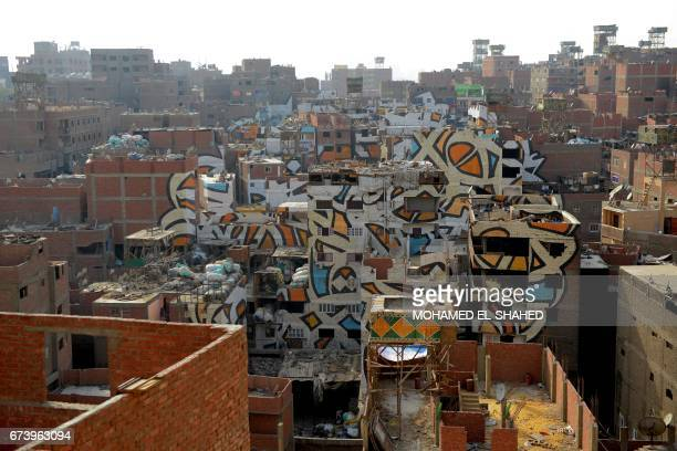 A picture taken on April 27 2017 shows graffiti work by Tunisian streetartist El Seed in the Zabalin area of the Egyptian capital Cairo The graffiti...