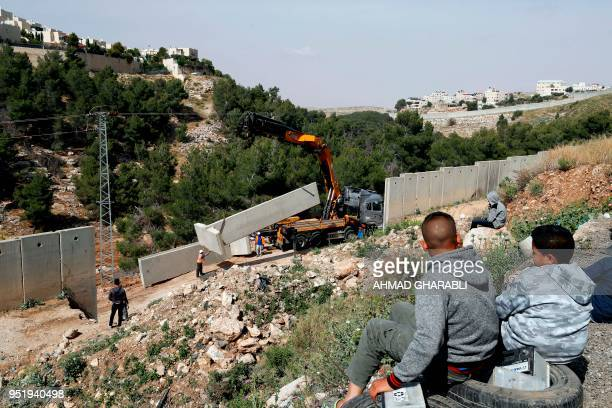 A picture taken on April 27 2018 shows Palestinians from the Shuafat refugee camp in east Jerusalem watching as Israeli forces replace the collapsed...