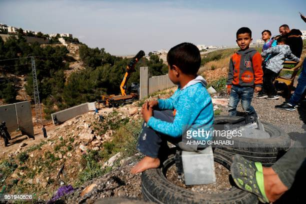 Picture taken on April 27, 2018 shows Palestinians from the Shuafat refugee camp in east Jerusalem watching as Israeli forces replace the collapsed...