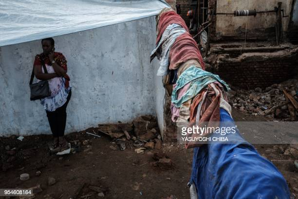 A picture taken on April 28 2018 shows victims' clothes being hung after being collected from a pit which was used as mass grave during 1994 Rwandan...