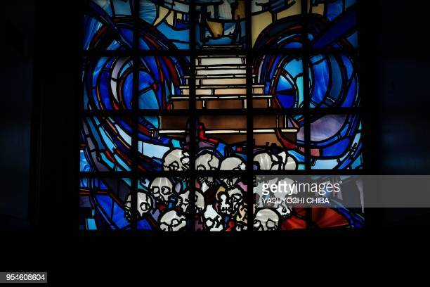 A picture taken on April 29 2018 shows a stainedglass at the Kigali Genocide Memorial in Kigali Rwanda According to the main association of the...